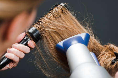blow dry: Close-up di parrucchiere, usando la spazzola per capelli e asciugacapelli