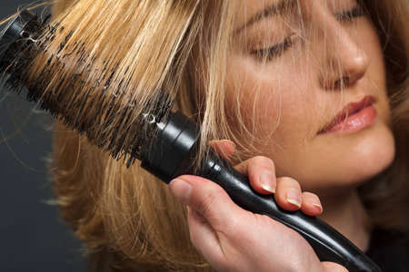 Close-up of hairdresser's hand styling customer's hair