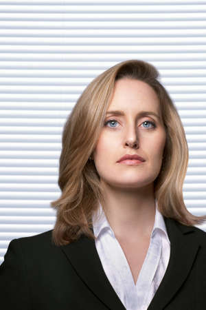 Portrait of female detective with serious facial expression infront of white slatted blinds
