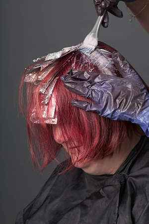 Close-up of hair stylist applying color to customer's hair