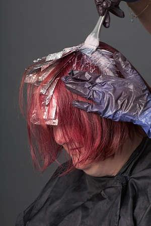 tinte cabello: Primer plano de estilista de cabello aplicar color al cabello del cliente