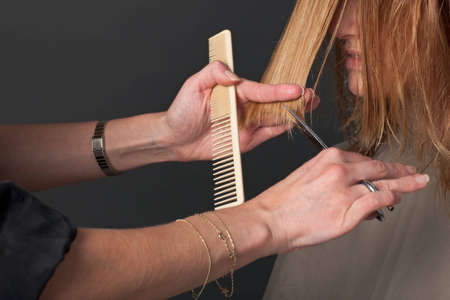 Hairdresser cutting customer's blond hair photo