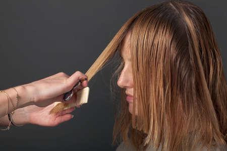 Hairdresser cutting blond hair of customer photo