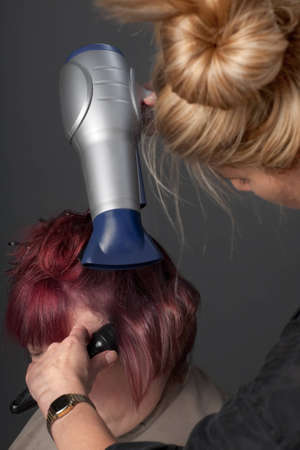 Hairdresser blow drying customers hair photo