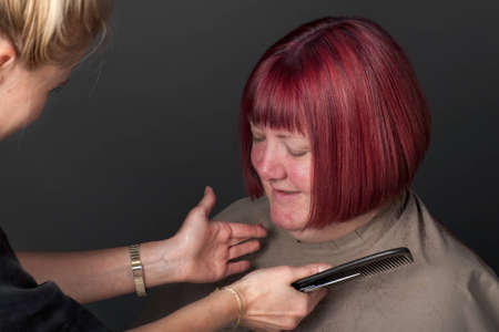 Hairdresser putting finishing touches to a client's hair photo