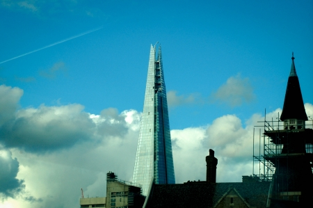 shard of glass: Tip of The Shard at London Bridge surrounded with buildings and clear sky Stock Photo