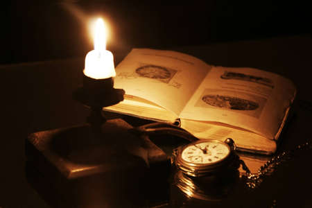 Candle clock and an old book Stock Photo