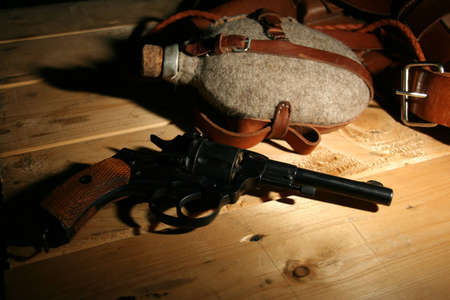 Revolver and an old jar lying on a wooden table Stock Photo - 10369935