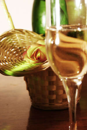 A glass of white wine on the background of roses and straw baskets photo