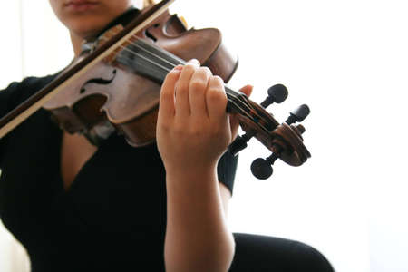 perform: A girl playing the violin