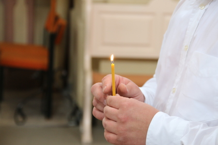 Boy in church holding a candle and pray Stock Photo