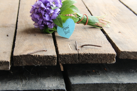thank you written on tag and a bouquet of violets