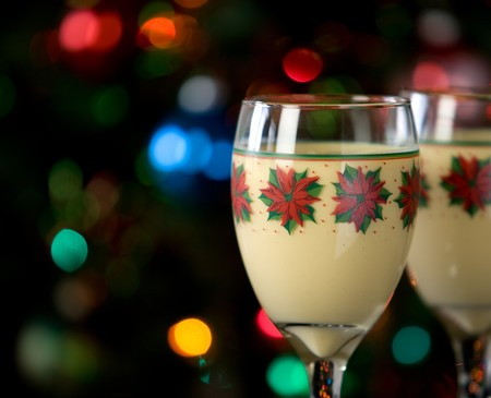 Two glasses of eggnog in festive holiday glasses in front of christmas tree with lights photo