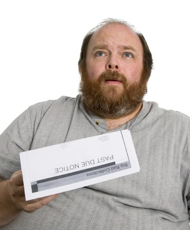 Man holding a past due notice and looking very worried photo