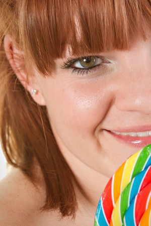 Red haired woman to lolipop - closeup. photo