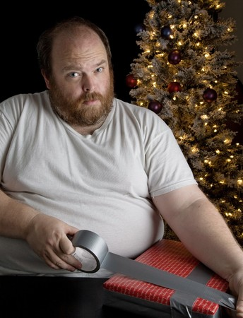 Obese man wrapping christmas present with duct tape photo