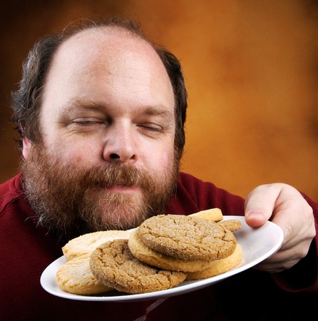 home health care: Overweight middle aged man with cookies Stock Photo