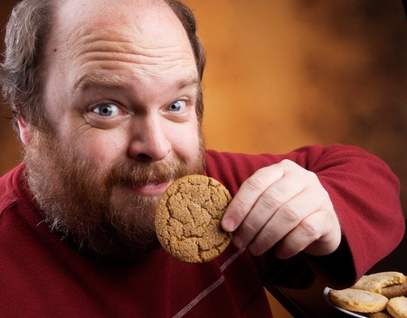 sobrepeso: Hombre de avanzada edad media con sobrepeso con cookies