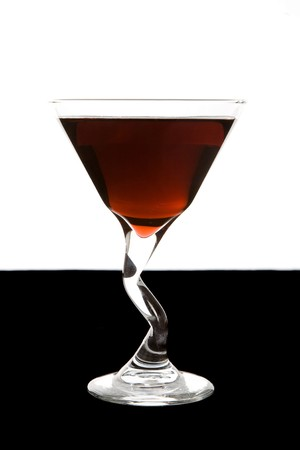 Filled martini glass against background.