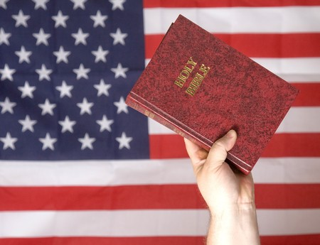 Upraised hand holding a bible in front of a flag