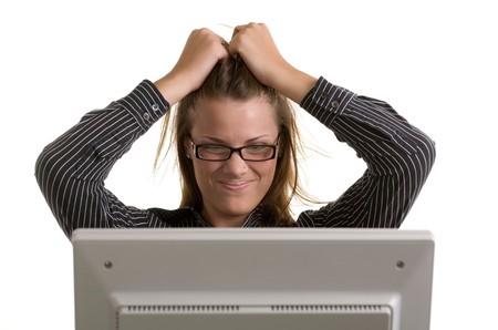 젊은 여자가 그녀의 얼굴을 문지르고 컴퓨터 충돌로 그녀의 머리카락을 당긴다.