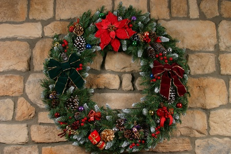 Home made holiday wreath hanging on stone wall photo