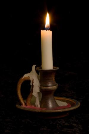 Candle in old fashioned candlestick holder on black background Standard-Bild