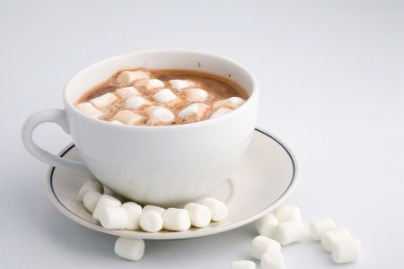 Cup of hot cocoa with marchmallows on white background