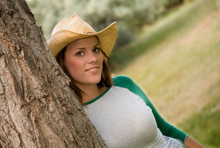 A young brunette in straw cowboy hat.  Narrow depth of field focusing on woman. photo