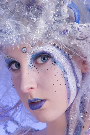Woman with heavy stage makeup looking like a winter fairy.