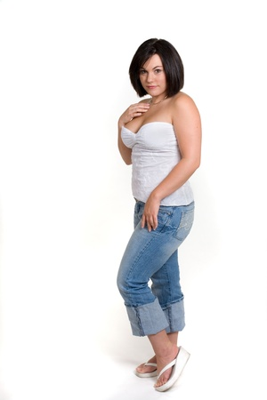 Cute young girl with full figure in jeans and white top