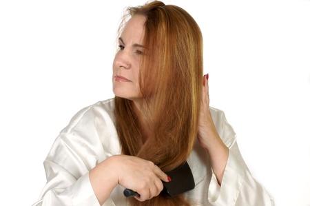 Woman brushing hair while wearing robe.  Shot in studio on white background 版權商用圖片