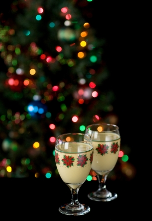 Two glasses of eggnog in front of christmas tree
