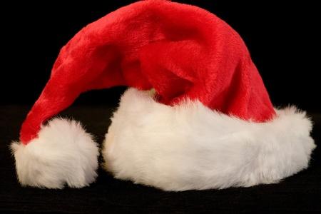 black backgound: Bright and furry Santa hat on black backgound Stock Photo