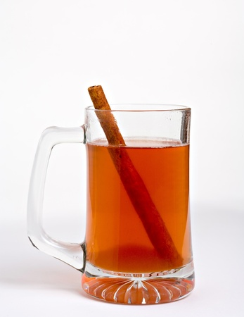 Hot apple cider in clear glass with cinnamon stick