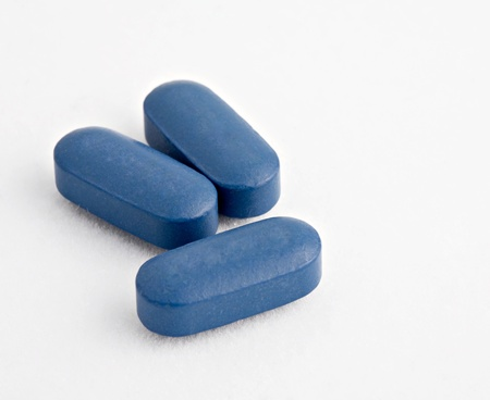 Macro shot of Three blue tablets on white