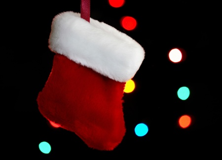 sized: Very small sized holiday stocking hanging with lights in background. Stock Photo