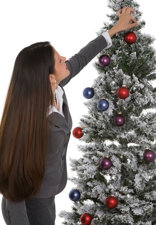 Businesswoman in suit decorating office christmas tree on white background.