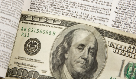 Closeup of 100 dollar bill and business in dictionary in dictionary