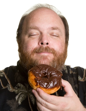 Middle aged and obese man about to eat a chocolate donut