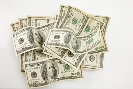 Multiple $100 bills in pile on white background