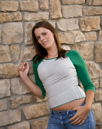 A young model poses next to a stone wall.