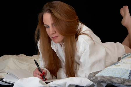 A woman writes in her diary while in bed photo