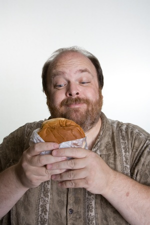 unhealthy: Overweight man in mid forties eating fast food