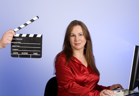 Woman with clapperboard in forground of image.