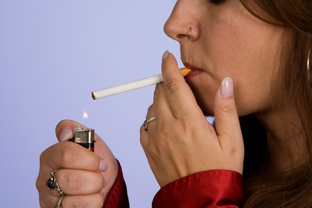 holding close: Close up of a woman lighting a cigarette with lighter