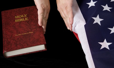Holding the bible away from the flag Standard-Bild