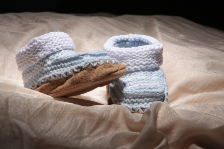 cuddly baby: Baby Booties knitted our of yarn with sewn to leather. Stock Photo