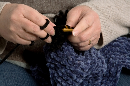 Close up on the hands of a mature woman knitting.