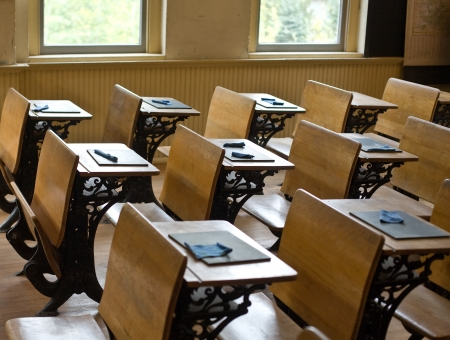Old classroom with antique chairs and desks with little blackboards on desks for writing.